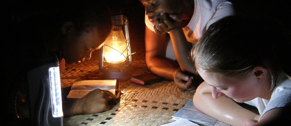 Heather Penman (right) shares a Bible reading by lamp light with children from Vanuoso Village, Gau Island, Fiji. She was one of two young women sent by the Bible Society in New Zealand to join a Dayspring Ministries team which travelled on the yacht ÂSeahawkto deliver Bibles to remote Fijian islands in September 2010. (project 86421)
