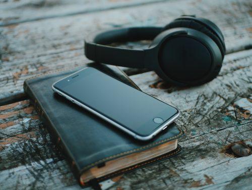 Raamattu, kännykkä ja kuulokkeet
