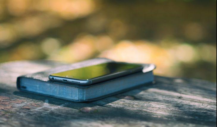 Pöydällä Raamattu, jonka päällä on kännykkä