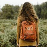 nainen reppu selässä pellolla