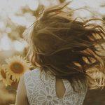 lapsi auringonkukkapellolla