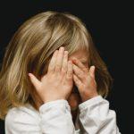 Lapsi pitää käsiä silmiensä edessä