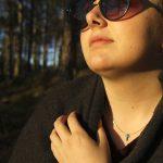 Rohkeus-ristiriipus kaulassa oleva nainen auringonlaskussa