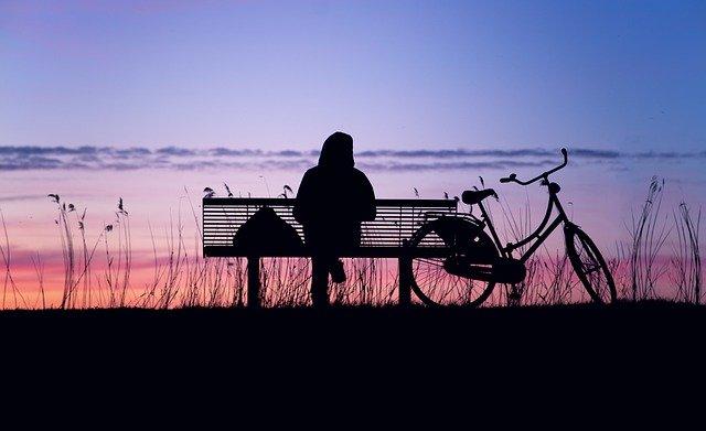 Pyöräilijä istumassa penkillä auringonlaskussa