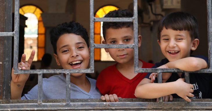 Kolme iloista egyptiläislasta katsoo ikkunasta